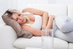 у девушке на диване болит живот