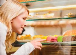 девушка смотрит на витрину с продуктами