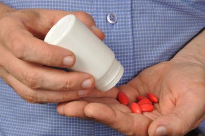 мужчина высыпал витамины на руку